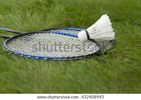 Shuttlecock with rackets on the green grass. Equipment for badminton. - stock photo