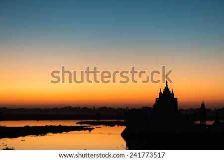 Shwe Modeptaw Pagoda as seen from the famous U Bein Bridge in Amarapura at sunset against a colorful sky - stock photo