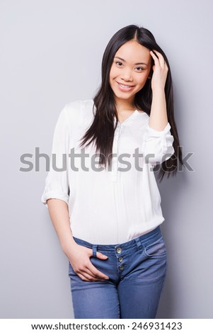 Shy beauty. Beautiful young Asian woman looking at camera and holding hand in hair while standing against grey background   - stock photo