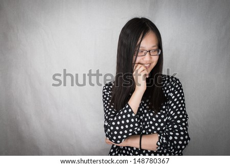 Shy girl smiling and biting nails, grey background - stock photo