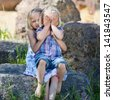 Shy little girl covering her face while sitting on the lap of her young sister posing for their portrait outdoors - stock photo