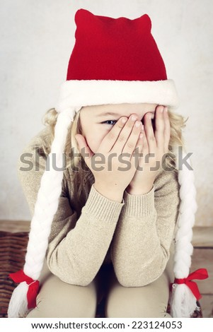 Shy little girl wearing santa's cap  - stock photo