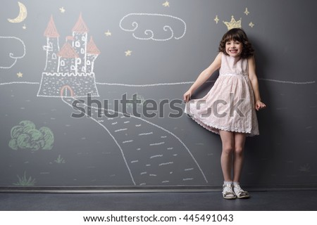 Shy smiling little princess is very pleased and happy to imagine herself the future queen. Depicted with chalk drawing with crown, road and castle on the grey wall. - stock photo
