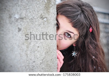 Shy woman hiding behind wall, face laughing timid - stock photo