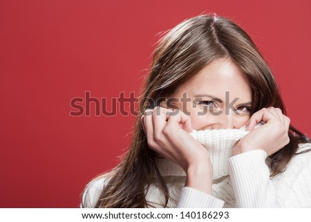 Shy young woman hiding inside the neck of her polo neck pullover while smiling at the camera, head and shoulders studio portrait on red - stock photo