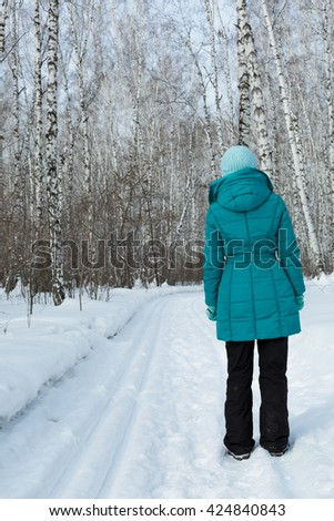 Siberia. A woman walks along the sky path in a birch forest on a Sunny day. - stock photo