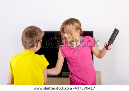 Siblings arguing over the remote control in front of the television. - stock photo
