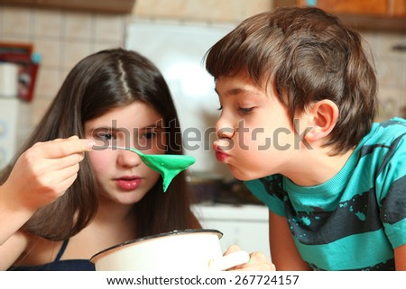siblings brother and sister experiment with food ingredients cook color cookies - stock photo