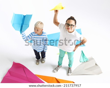 Siblings, brother and sister reassembles origami .Siblings, a girl and a boy throwing paper airplane  - stock photo