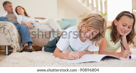 Siblings doing their homework on the carpet with their parents behind them - stock photo
