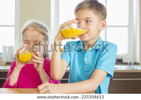 Siblings drinking orange juice in kitchen at home - stock photo