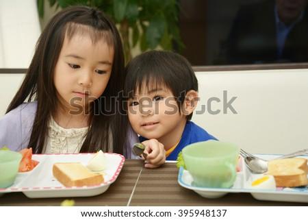 Siblings eating breakfast - stock photo
