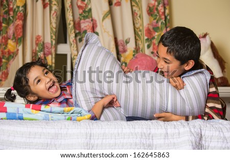 Siblings Enjoying a Pillow Fight - stock photo