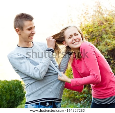 Siblings fighting, brother pulling his sister's hair. - stock photo