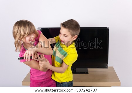 Siblings fighting over the remote control in front of the TV - stock photo