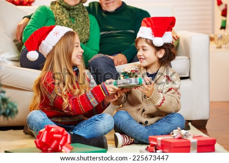 Siblings giving gifts to each other at christmas at their grandparents - stock photo