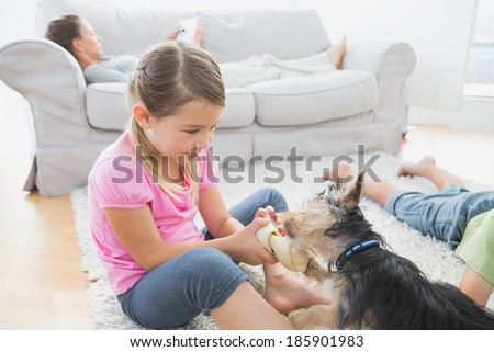 Siblings lying on rug with their yorkshire terrier at home in the living room - stock photo