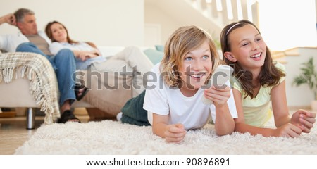 Siblings lying on the floor watching tv together - stock photo