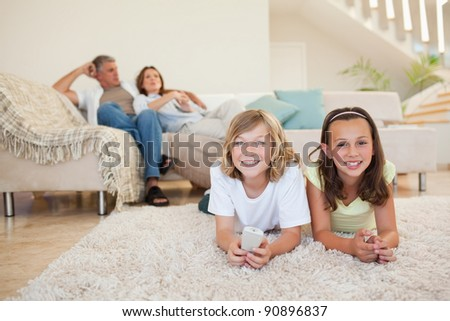 Siblings on the floor watching tv together - stock photo