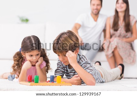 Siblings playing board game on the floor with parents sitting behind them - stock photo