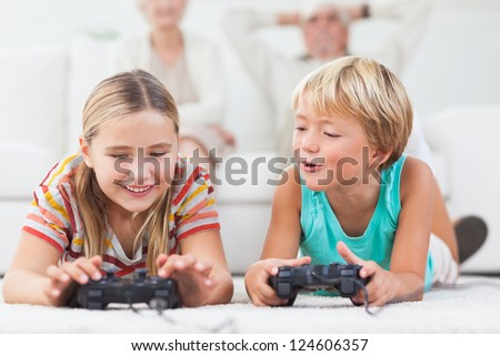 Siblings playing video games on the floor - stock photo