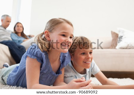 Siblings playing video games while their parents are watching in a living room - stock photo