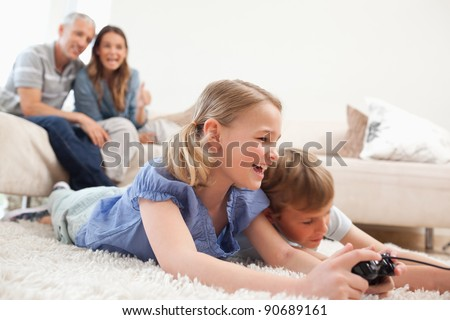 Siblings playing video games with their parents on the background in a living room - stock photo