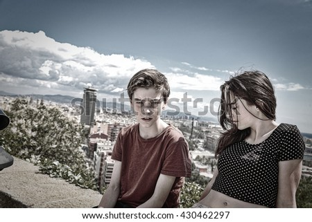 siblings sitting on a wall with Barcelona in background - stock photo