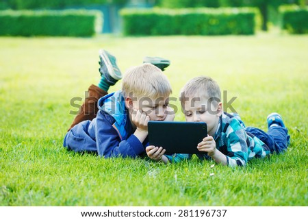 Siblings using a tablet, yingon grass in the park in suny day - stock photo