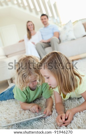 Siblings using tablet together on the carpet with parents behind them - stock photo