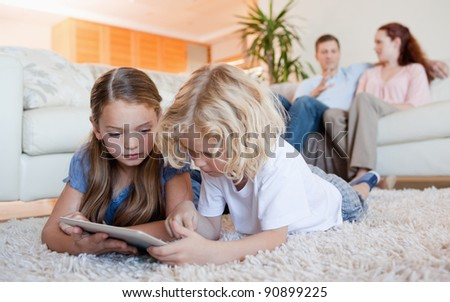 Siblings using tablet together on the living room floor - stock photo
