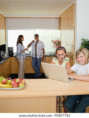 Siblings with their laptop in the kitchen with parents behind them - stock photo