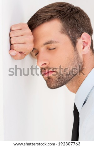 Sick and tired. Side view of depressed young man in shirt and tie leaning at the wall and keeping eyes closed - stock photo