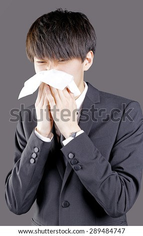 Sick asian businessman blowing his nose on blackground - stock photo