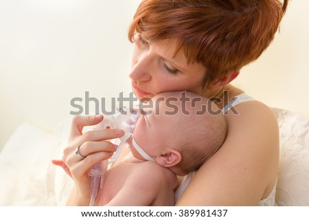 Sick baby of 7 weeks old getting treatment with nebuliser or aerosol - stock photo