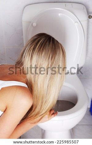 Sick blonde woman in the toilet - stock photo