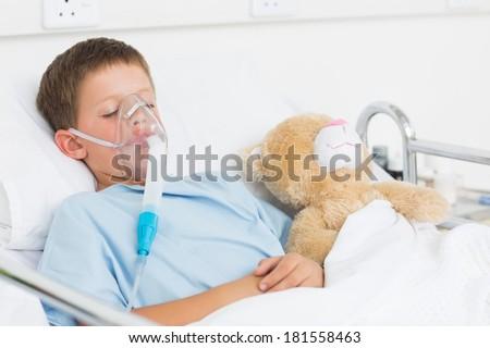 Sick boy wearing oxygen mask sleeping beside teddy bear in hospital bed - stock photo