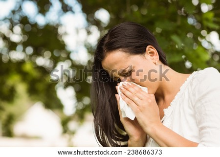 Sick brunette blowing her nose in the park - stock photo