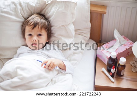 Sick child boy lying in bed with a fever, resting - stock photo