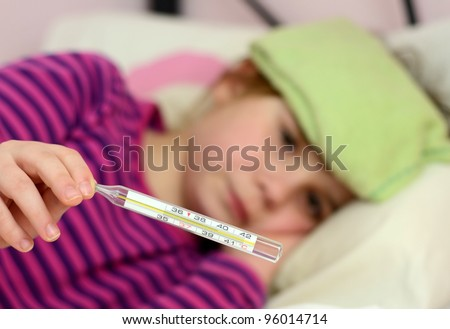 Sick child girl showing big fever on thermometer - stock photo