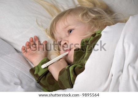 sick child in bed under blanket with thermometer in mouth - stock photo