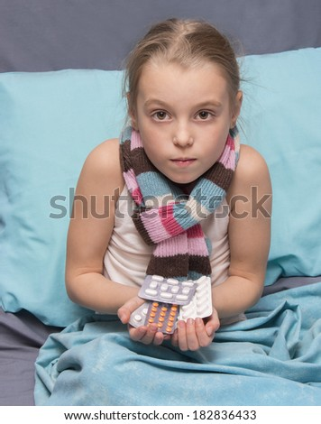Sick child with pills in hands sitting in a bed - stock photo