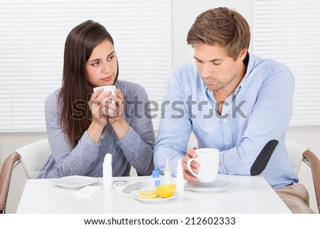 Sick couple drinking lemon tea while sitting at table in house - stock photo