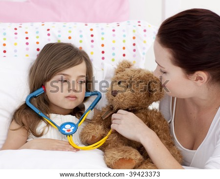 Sick daughter playing with a stethoscope with her mother in bed - stock photo