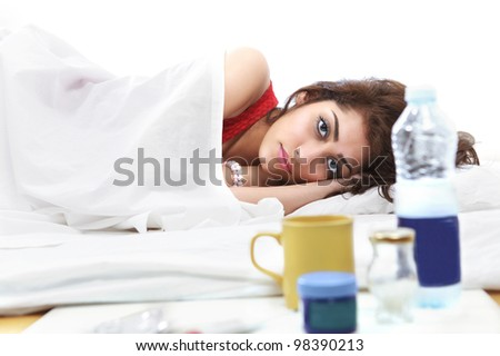 Sick girl in bed with medicines and fluids in foreground - stock photo