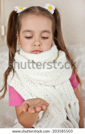 Sick girl in scarf looks at his hand - stock photo