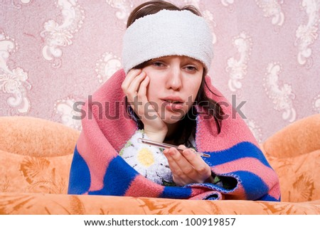 sick girl with a thermometer at home on the couch - stock photo