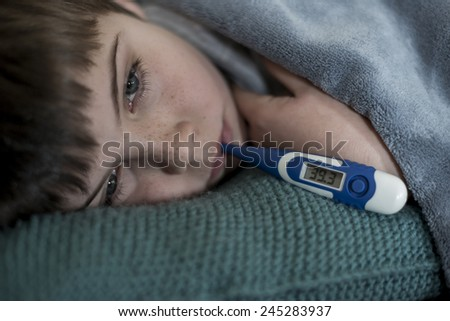 sick little boy with thermometer in his mouth - stock photo