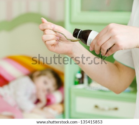 Sick little girl awaits her medication pouring in a spoon in the foreground - stock photo