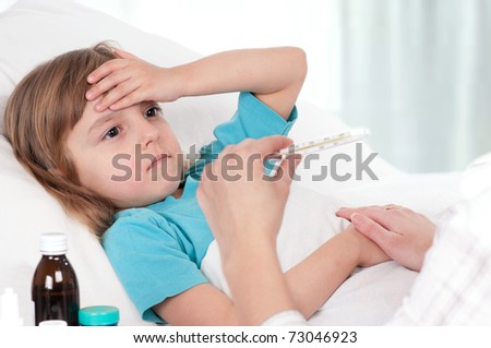 Sick little girl in bed. Mother with thermometer is sitting near the bed. - stock photo